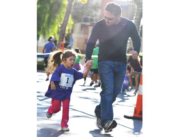 Olivia Becker, 3, and her father, Marc Becker, run the Kid K along Town Center Drive, part of the festivities at the Santa Clarita Marathon in Valencia on Sunday.
