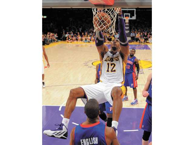 Los Angeles Lakers center Dwight Howard, top, dunks against the Detroit Pistons on Sunday in Los Angeles.
