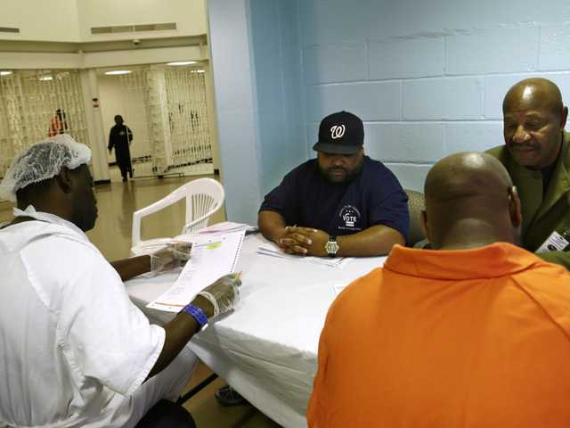 In this photo taken Oct. 24, 2012, Arlin Budoo, center, and Tyrone Parker, right, help prisoners to vote at the D.C. Jail in Washington.