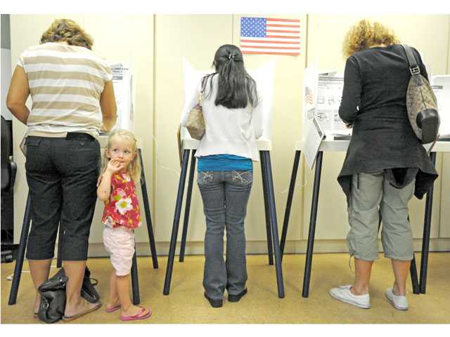 Faith Hilton, 2, accompanies her grandmother Patty Rake, of Newhall, left, at a polling place at the Santa Clarita Valley Senior Center in Newhall on Tuesday. (Jonathan Pobre/The Signal)
