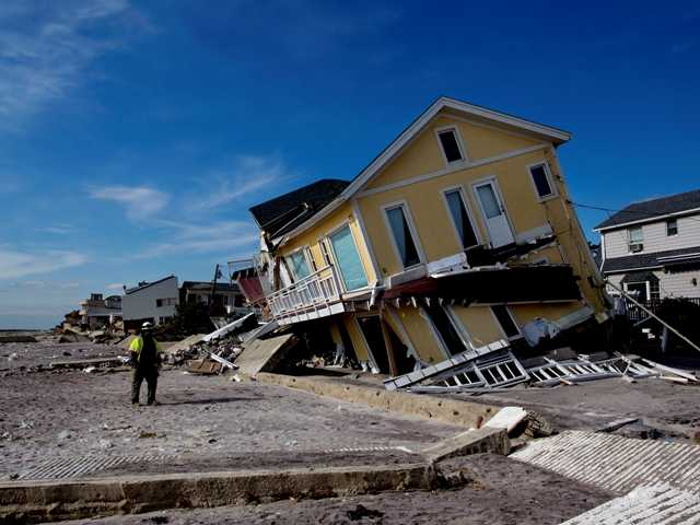 A damaged home tilts to one side along the beach in the Belle Harbor section of the borough of Queens, New York, in the wake of Superstorm Sandy on Nov. 5.