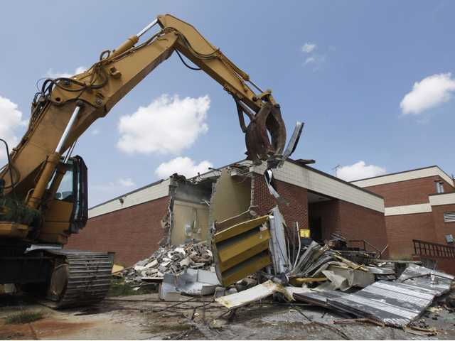 A demolition machine begins the demolition of the Louisa County High School in Mineral, Va., on Aug. 21. The school was damaged beyond repair during the earthquake last year.