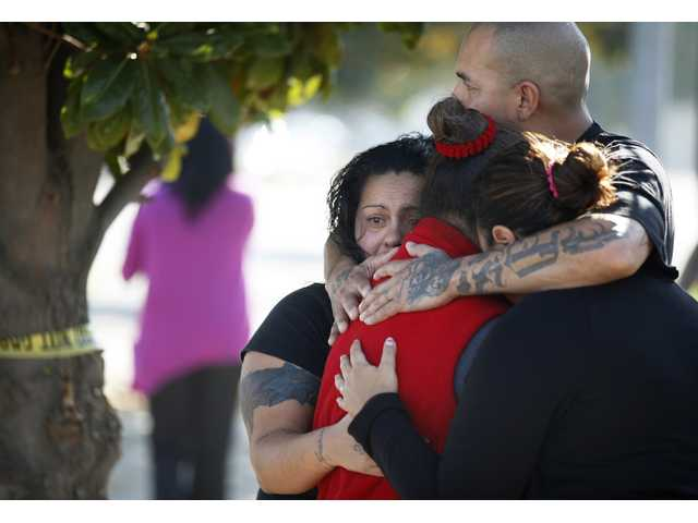 Three women and a man hug outside the police perimeter in central Fresno where a shooting occurred at a workplace Tuesday. A parolee who worked at a chicken processing plant opened fire at the business on Tuesday.