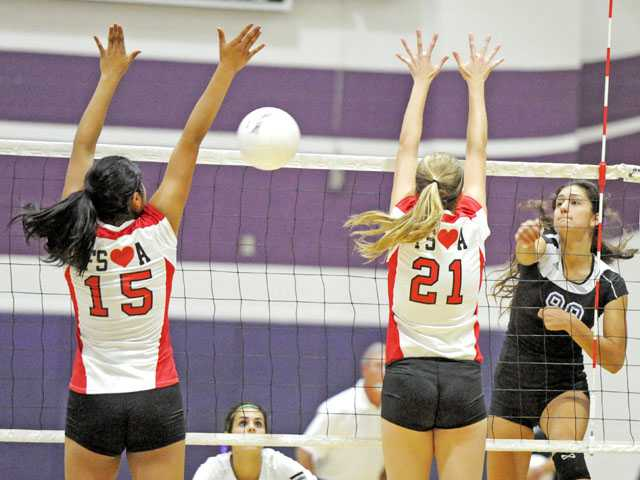 Valencia's Sierra Sanchez, right, hits between Flintridge Sacred Heart defenders Megan Bacall (15) and Kathryn Conley (21) on Tuesday night at Valencia High in the first round of the CIF-SS Div. IA playoffs.