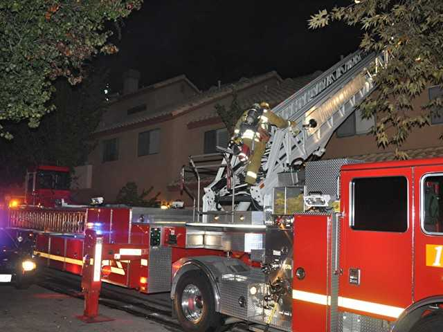 Firefighters ascend aerial ladder to roof of condominium building fire early Wednesday in Saugus. Investigators say they believe the fire was deliberately set. Photo by Rick McClure/For The Signal