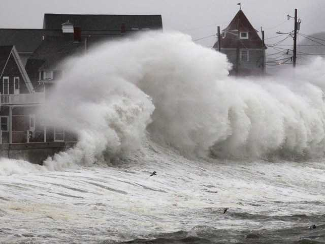 Waves crash into a seawall and buildings along the coast in Hull, Mass., Wednesday. A high-wind warning is in effect in the state until Wednesday night, with gusts of up to 60 mph expected in some costal areas.