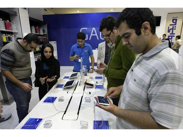Potential customers try out Samsung cell phones and tablet computers in a store, in Tehran, Iran, Thursday.