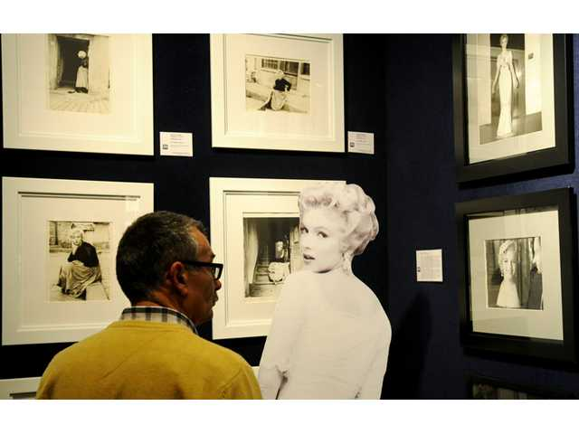 A potential bidder looks at Marylin Monroe photos prior to an auction of pictures by the late celebrity photographer Milton H. Greene.