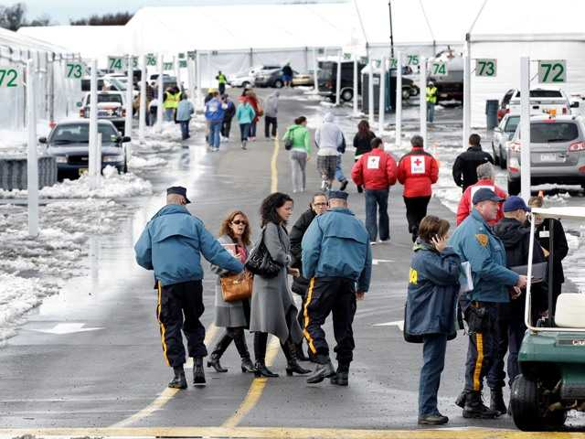 New Jersey Commissioner of the Department of Human Services, Jennifer Velez, center, walks near rows of large tents Thursday, Nov. 8, 2012, in Oceanport, N.J.. Sandy evacuees are being moved into to tent-like housing.