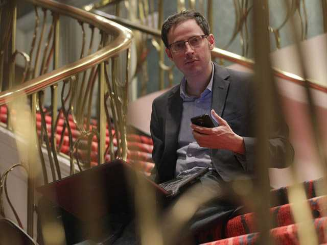 Nate Silver holds his phone as he sits on the stairs with his laptop computer at a hotel in Chicago on Friday.
