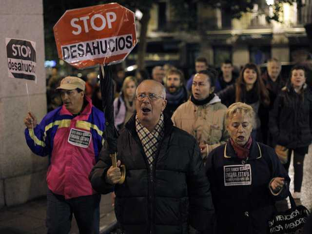 "People hold banners that read: ""Stop Evictions"", during a march against evictions, in Madrid."