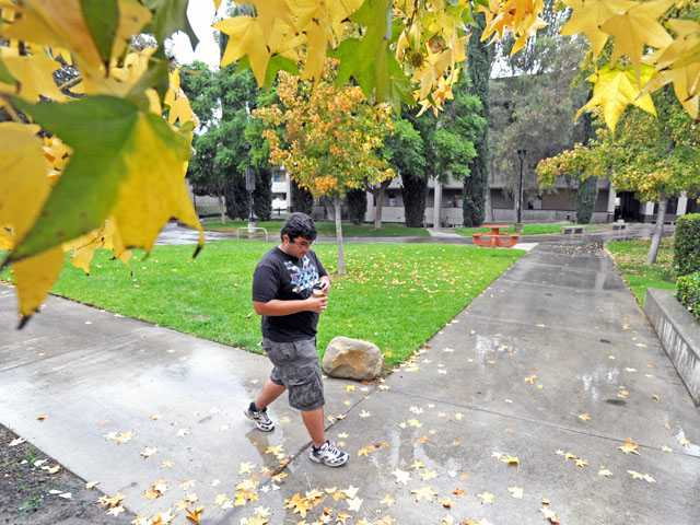 Biology student Roger Tadros, 18, walks through a rain-slicked path at College of the Canyons' Valencia campus on Thursday.