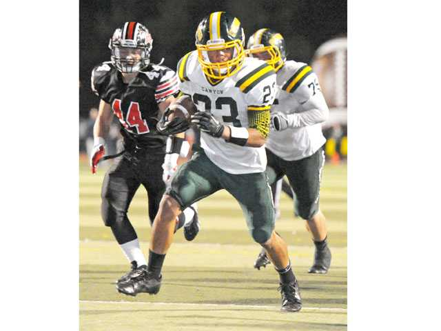 Canyon's Myron McAfee (23) runs the ball last Friday.