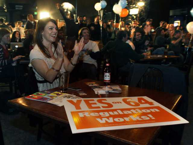 In this Tuesday  photo, Amanda Jetter celebrates along with others attending an Amendment 64 watch party in a bar in Denver.