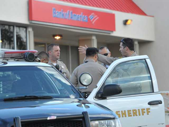 L.A. County Sheriff's Deputies meet in front of the Bank of America branch at the corner of Seco Canyon Road and Bouquet Canyon Road in Saugus after the bank was robbed on Friday morning.