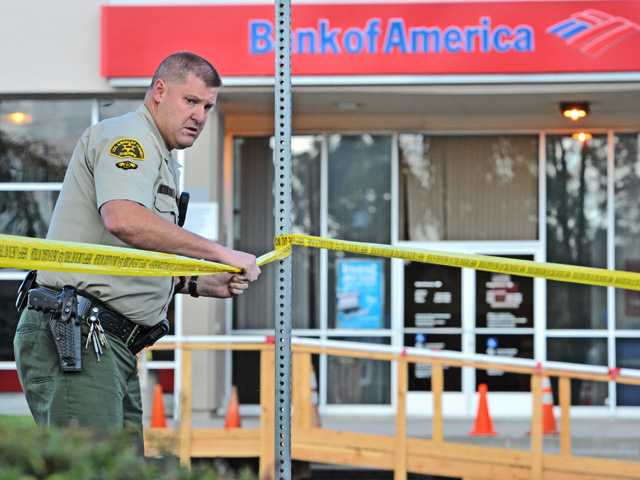 L.A. County Sheriff's Deputies cordon off the the parking lot in front of the Bank of America branch at the corner of Seco Canyon Road and Bouquet Canyon Road in Saugus after the bank was robbed on Friday morning.