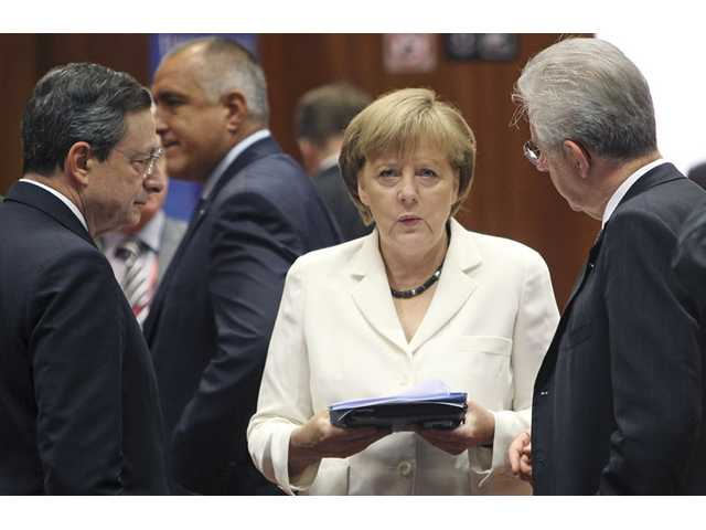 German Chancellor Angela Merkel, center, speaks with European Central Bank President Mario Draghi, left, and Italian Prime Minister Mario Monti.