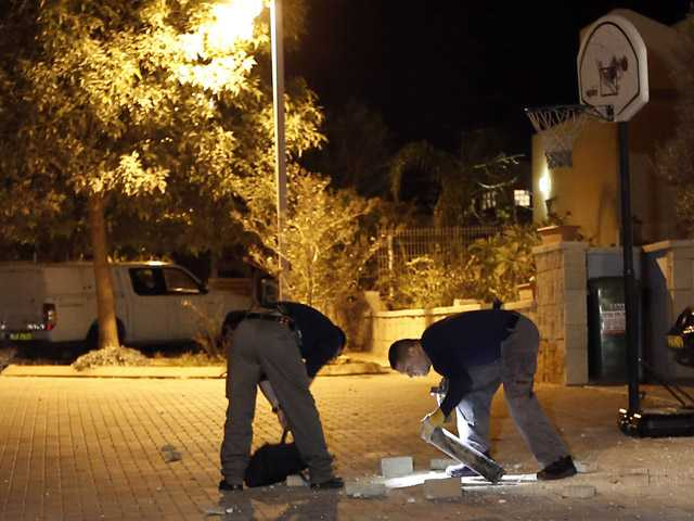 Israel police explosives experts collect a Qassam rocket at a residential area near the Israel-Gaza border in southern Israel.