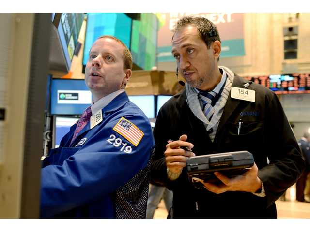 Robert Nelson II of Barclays, left, and Fady Tanios of Raven Securities work on the floor of the New York Stock Exchange.
