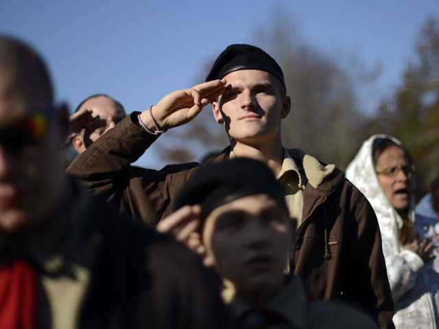 Boy Scout Michael Demanche, of Mashpee, Mass., salutes the flag during a ceremony held at the National Cemetery in Bourne, Mass., on Saturday.