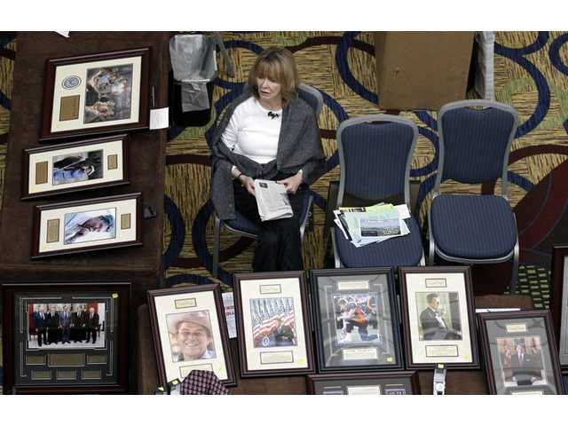 Kay Aaron waiting for customers at a booth selling pictures of Republican leaders and icons during the California Republican Party convention.