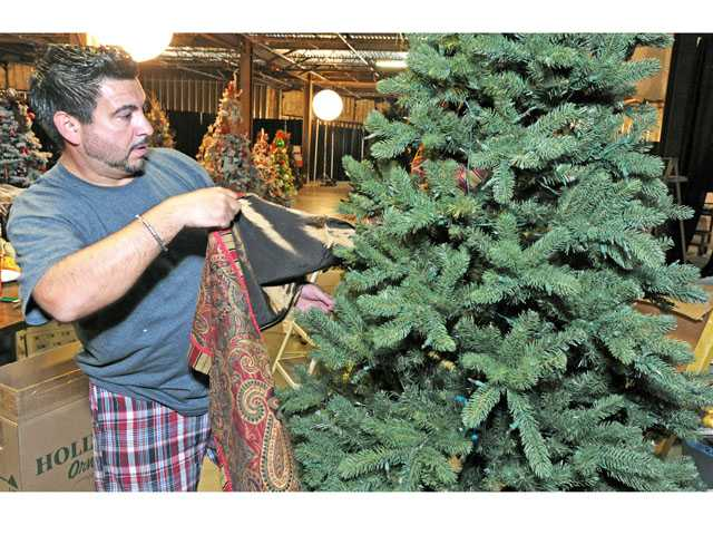 Interior designer Ruben Haynes uses a table runner as he begins to decorate a Christmas tree in preparation for the Festival of Trees. Haynes designed and decorated more than 20 of the 39 full-size trees on display.