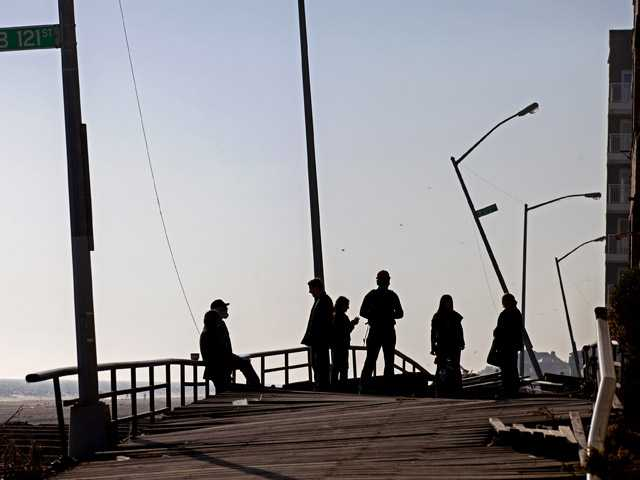 People gather on the buckled boardwalk of the Rockaway Park neighborhood of the borough of Queens.