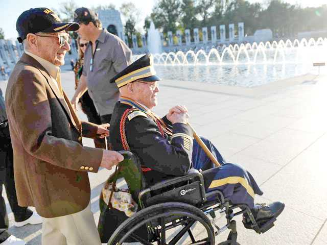 "Navy veteran Otto Werner pushes retired Army Capt. Emmett ""Rosy"" Nolan, in wheelchair, at the World War II memorial."