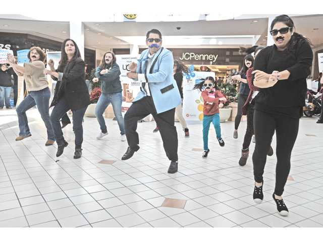 Members of a flash mob wearing fake mustaches dance to bring awareness to men's cancer issues in the Westfield Valencia Town Center mall on Saturday.
