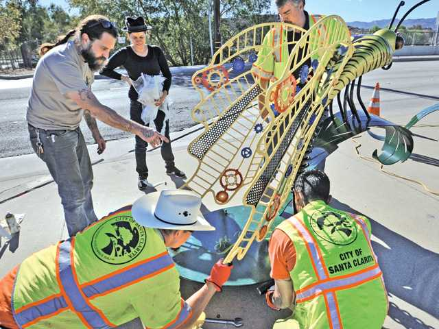 Sculptor LT Mustardseed, center, looks on as fabricator Chris Barber directs Santa Clarita workers as they install her sculpture near Central Park in Saugus on Saturday.