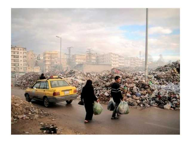 Syrians carry their rubbish to a mountain of garbage in a roundabout in Aleppo, Syria. Due the heavy fighting and shelling, the garbage collection system collapsed weeks ago.