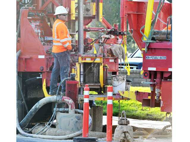 Alberto Vega of National Exploration, Wells & Pumps works to drill a monitoring well on Auto Center Drive near Creekside Road in Valencia on Wednesday.