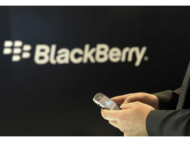 A Blackberry employee holds a mobile phone of Blackberry in Berlin.