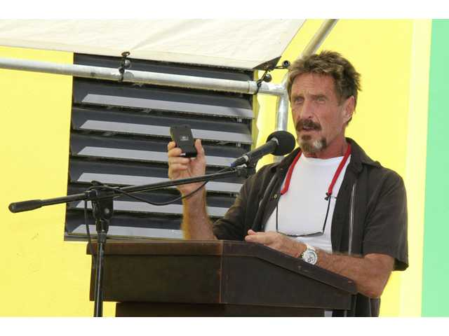 "John McAfee speaks at the official presentation of equipment ceremony that took place at the San Pedro Police Station in Ambergris Caye, Belize. McAfee, 67, has been identified as a ""person of interest"" in the killing of his neighbor, 52-year-old Gregory Viant Faull, whose body was found on Sunday. Police are urging McAffe to come in for questioning."