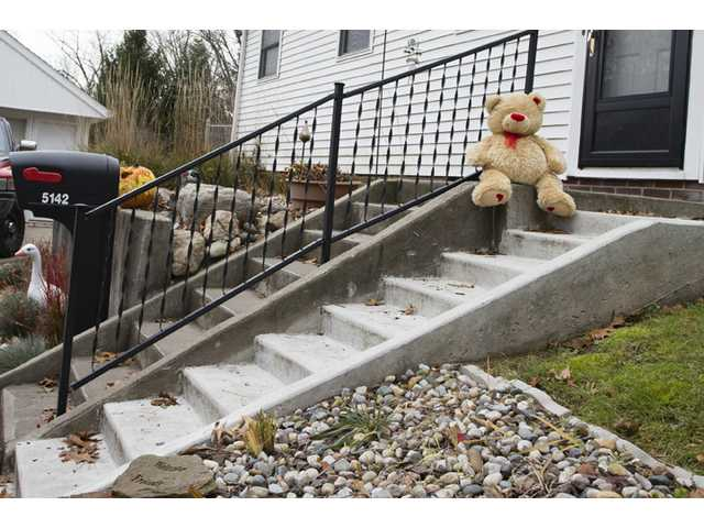 A lone teddy bear sits on the steps of the home where three children, their uncle, and their grandmother were found dead inside a garage Monday.