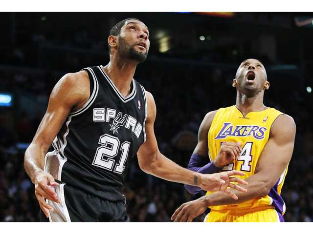 Los Angeles Lakers guard Kobe Bryant (24) and San Antonio Spurs center Tim Duncan (21) watch a shot on Tuesday in Los Angeles.