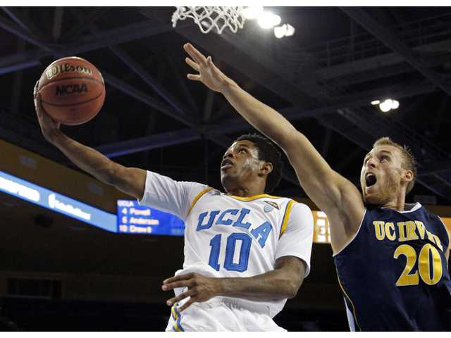 UCLA guard Larry Drew II (10) goes for a layup as UC Irvine's Adam Folker (20) defendson Tuesday in Los Angeles.