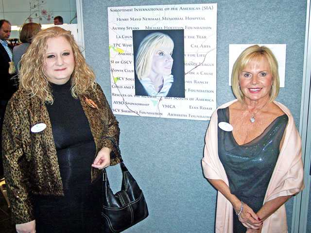 "Artist Michele Thompson, left, with ""iconic"" woman Cheri Fleming and the work of art created by Thompson for the Single Mothers Outreach fundraiser."