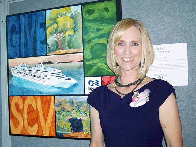 Julie Benson with Kimberly Winberry's artwork reflective of her job as Princess Cruises vice president of Public Relations.