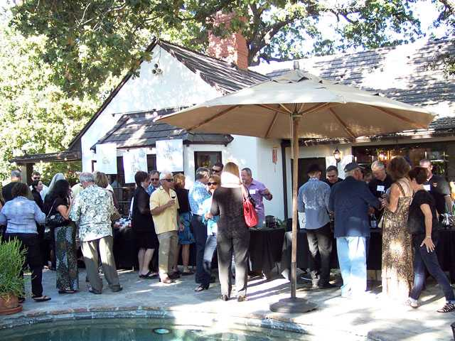 Guests mingle poolside at the Sunset in the Vineyard wine tasting fundraiser.
