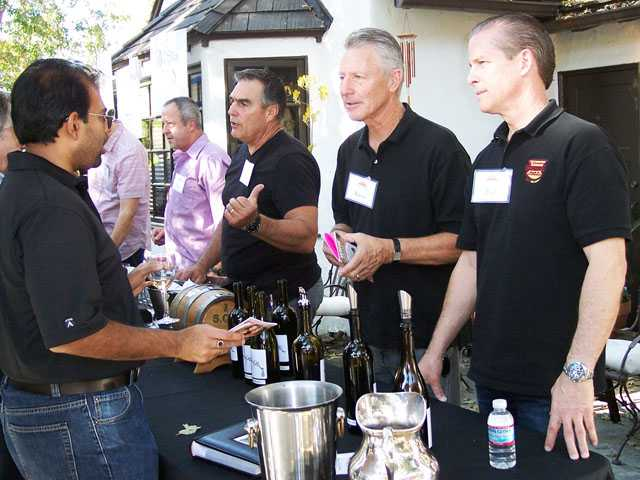 Guests sample wine from Chris Carpenter of Compa Vineyard, third from right and Kevin and Paul Browne, right.