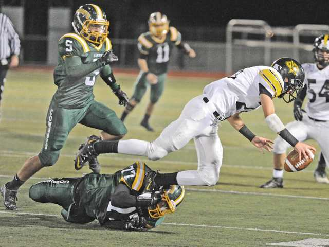 Canyon's Jacob Clarke (77) sacks the San Luis Obispo quarterback on Nov. 9 at Canyon High School.