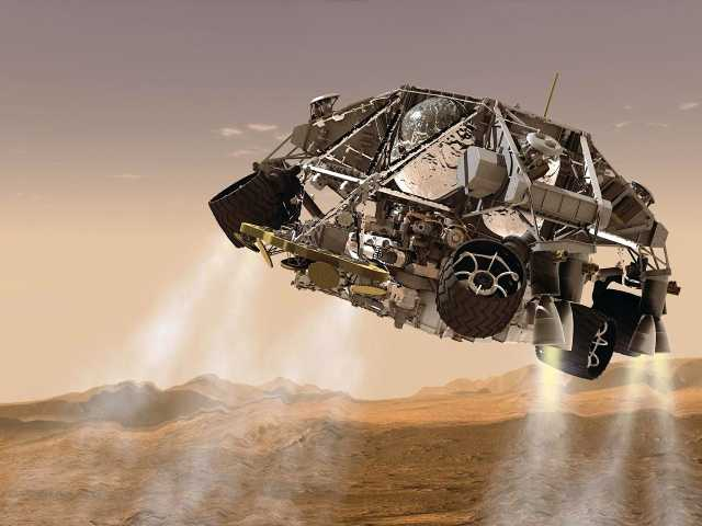 This artist's concept provided by NASA/JPL-Caltech via the Rockford Register Star, shows the rover and descent stage for NASA's Mars Science Laboratory spacecraft during the final minute before touched down.