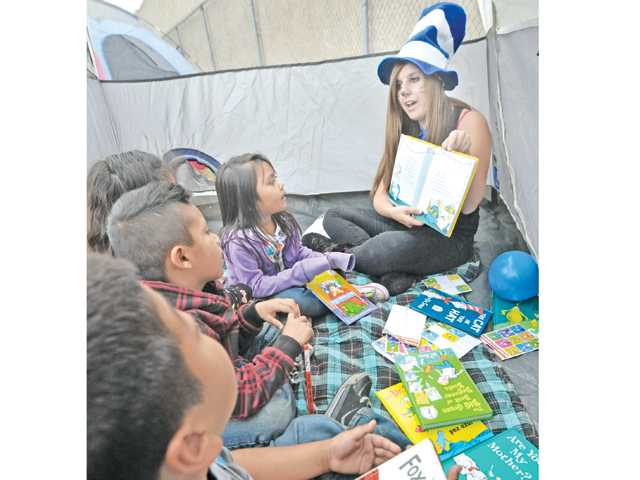Hart High School senior Erica Bruckner reads from a Dr. Seuss book in a camping tent to 50 preschool students who attended the Camp Read Aloud event held at Volunteers of America preschool in Newhall on Thursday. Bruckner staged the literacy fair as her Girl Scout Gold Award program. For more photos, see A7.