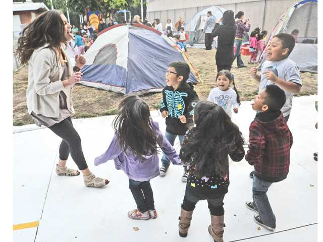 Hart High School senior Brittany Hartmire, left, leads a sing-and-dance-a-long with some the 50 preschool students who attended the Camp Read Aloud literacy fair event held at Volunteers of America preschool in Newhall on Thursday.