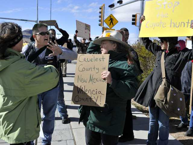 Esteban Marquez, second from left, a supporter of the coyote hunting contest, engages in a heated discussion on Saturday with protester Jean Crawford, center, in Los Lunas, N.M.