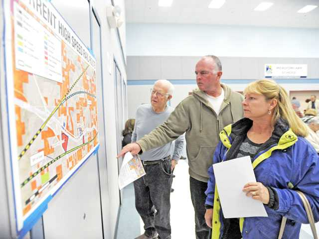 From left, Don Widell, Mike Harrington and Sally Harrington look at a map of the project at Meadowlark Elementary School in Acton on Thursday.