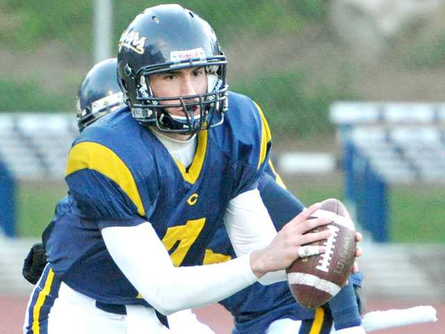 College of the Canyons quarterback Ryan Kasdorf takes a snap during Saturday's game against Allan Hancock College at COC.