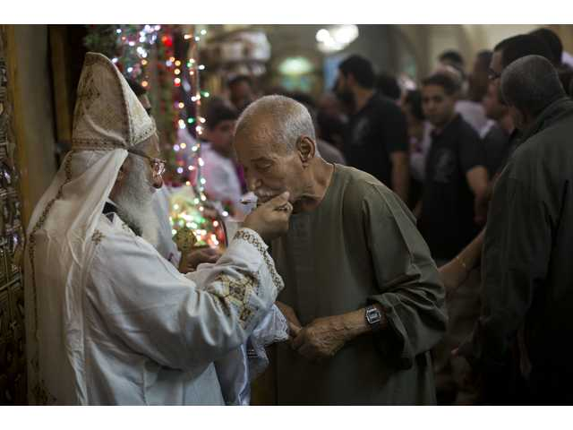 A Coptic pilgrim in Egypt attends a Mass this week during a moulid at Mar Girgis Monastery, near Luxor, Egypt.