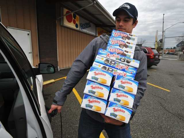 Andy Wagar loads Twinkies, Ho-Hos and Cup Cakes into a van outside the Wonder Bakery Thrift Shop in Bellingham, Wash., Friday, Nov. 16, after Hostess Brands Inc. said it would shutter its operations.